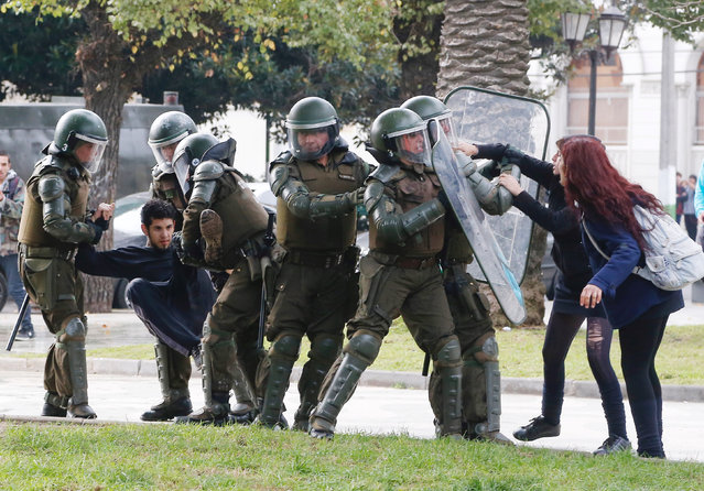 A demonstrator is detained as others clash with riot police during an unauthorized march called by secondary students to protest against government education reforms in Valparaiso, Chile, May 26, 2016. (Photo by Rodrigo Garrido/Reuters)