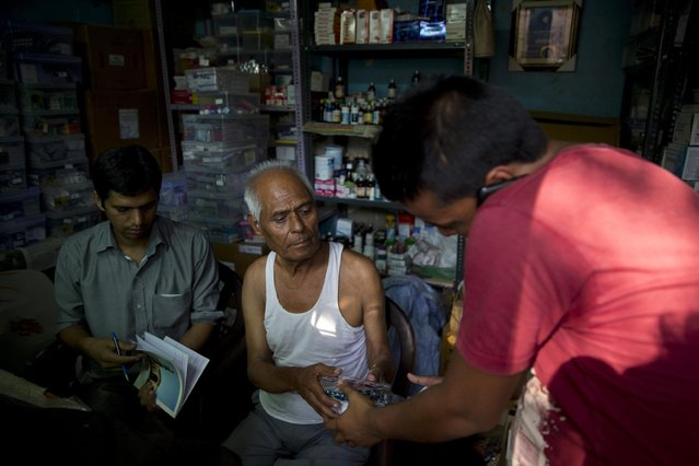 """In this June 8, 2015 photo, Omkarnath, center, who goes by the name """"Medicine Baba"""", gives medicine to the relative of a severely ill patient at his rented medicine store room in New Delhi, India. (Photo by Saurabh Das/AP Photo)"""