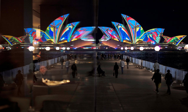 The Sydney Opera House, featuring projected art, is reflected in a hotel window during the opening night of the annual Vivid Sydney light festival in Sydney, Australia, May 27, 2016. (Photo by Jason Reed/Reuters)