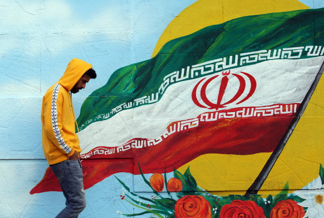 An Iranian walks next a wall painting of Iranian national flag, Tehran, Iran, 17 November 2019. According to reports, internet access has been limited in the country amid protests over increasing fuel price in Iran. (Photo by Abedin Taherkenareh/EPA/EFE)