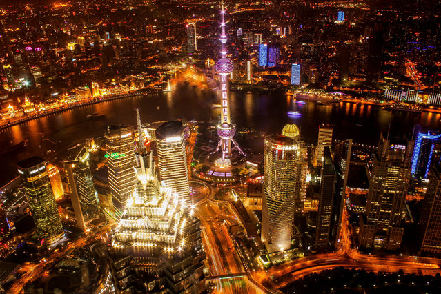 """""""Shanghai Nightline"""". This is the shot I came to Shanghai for. I waited till night to buy my ticket to the top of the World Financial Center to capture the intensity and sprawling size of China's metropolis. Photo location: Shanghai, China. (Photo and caption by Collin Hadley/National Geographic Photo Contest)"""