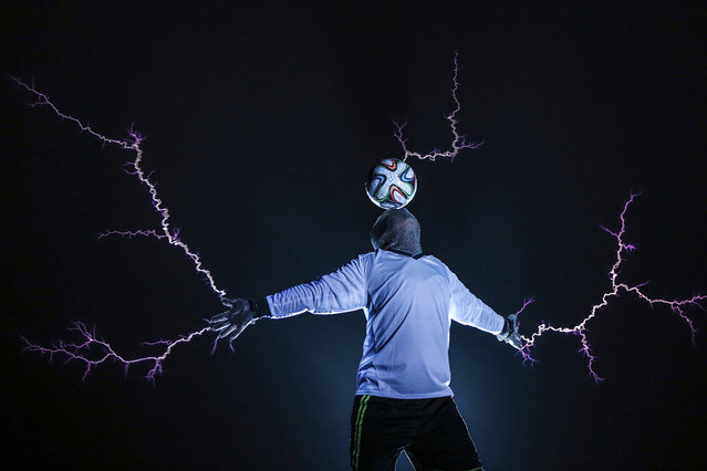 A member of the Thunderbolt Craziness band wearing a metal suit balances a soccer ball on his head as electricity is discharged from Tesla coils during a performance to celebrate the 2014 Brazil World Cup, in Changle, Fujian province June 12, 2014. The band specialises in producing electric arcs from Tesla coils that have been charged with one million volts of electricity. (Photo by Reuters/Stringer)