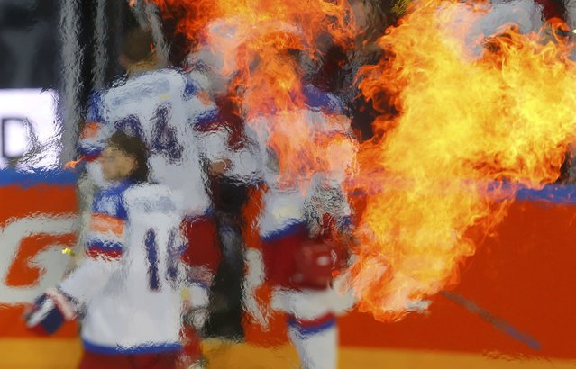 Russian players are seen through the haze of flames as they leave the rink after losing their Ice Hockey World Championship final game against Canada at the O2 arena in Prague, Czech Republic May 17, 2015. (Photo by Laszlo Balogh/Reuters)