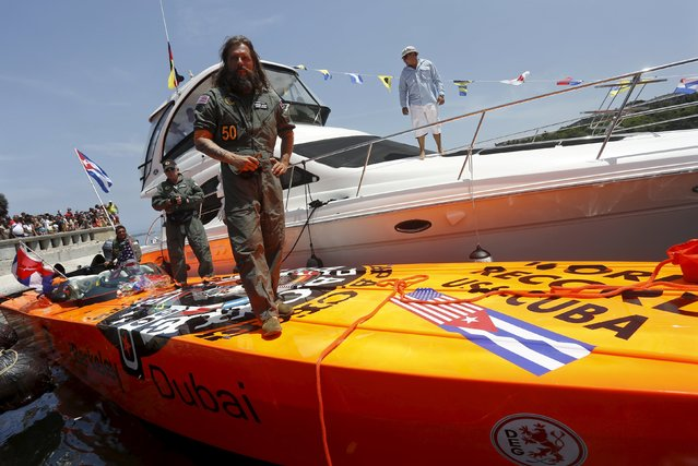 German powerboater Roger Kluh stands on his orange Apache Star speedboat after arriving in Havana from Key West in under 2 hours, setting a new speed record for an event that last took place 57 years ago, August 1, 2015. Kluh and his crew traversed the 100 miles (160 km) between Key West and Havana in about 1 hour and 45 minutes, beating the 6-hour-23-minute record set by an American in 1958. (Photo by Reuters/Stringer)