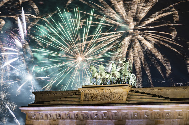 Fireworks light the sky above the Quadriga at the Brandenburg Gate during New Year celebrations in Berlin, Germany, Wednesday, January 1, 2020. Hundred thousands of people celebrated New Year's Eve welcoming the new year 2020 in Germany's capital. (Photo by Christophe Gateau/dpa via AP Photo)