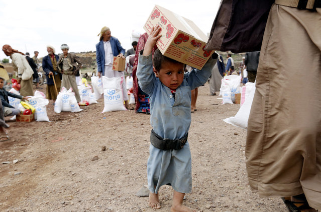 A conflict-ridden Yemeni child carries food rations provided by Mona Relief Yemen at a village on the outskirts of Sana'a, Yemen, 27 August 2019. The ongoing conflict in Yemen since 2015 has created the worst humanitarian crisis in the world, where some 80 percent of Yemen's 26-million population are in need of humanitarian assistance. (Photo by Yahya Arhab/EPA/EFE)