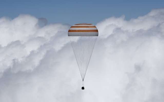 The Soyuz TMA-19M capsule carrying NASA's Tim Kopra, Tim Peake of the European Space Agency and Russian agency Roscosmos' Yuri Malenchenko descends beneath a parachute near the town of Dzhezkazgan, Kazakhstan, Saturday, June 18, 2016. A three-person crew from the International Space Station has landed safely in the sun-drenched steppes of Kazakhstan. (Photo by Shamil Zhumatov/Pool Photo via AP Photo)