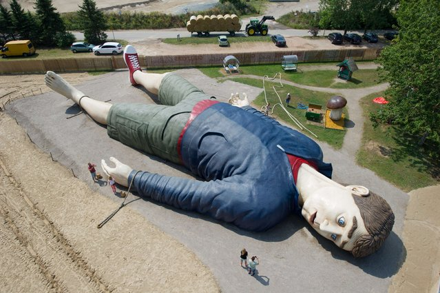 "Workers work at the ""Gulliver"" sculpture on July 8, 2014 in the amusement park ""Gulliver's World"" in Pudagla, on the island of Usedom, Germany. The sculpture of ""Gulliver in Lilliput"" is 36 meters long and 17 meters wide, which is one of the largest of its kind in Europe. The sculpture will be shown from July 11, 2014. (Photo by Stefan Sauer/AFP Photo/DPA)"