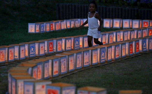 A girl runs among paper lanterns in remembrance of atomic bomb victims on the 70th anniversary of the bombing of Nagasaki, in western Japan, August 9, 2015, on the 70th anniversary of the bombing of the city.  A bell tolled in Nagasaki on Sunday morning as the Japanese city marked 70 years since the dropping of the last atomic bomb on a civilian target in the closing days of World War Two. (Photo by Toru Hanai/Reuters)