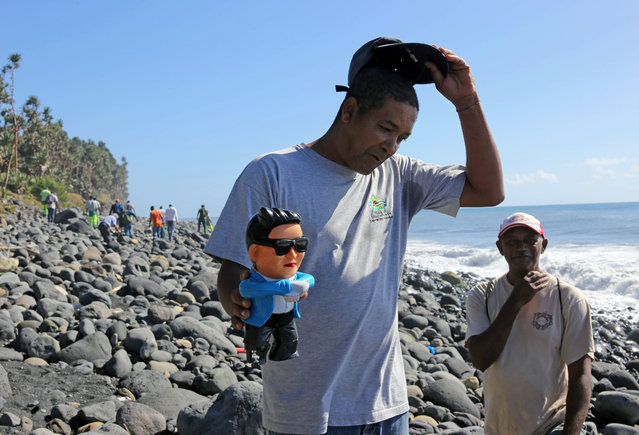 An employee shows a figurine of South-Korean singer Psy found during a search of employees of environmental protection and coastal cleanup organisations for debris from the ill-fated Malaysia Airlines flight MH370 on a beach in Sainte-Marie de la Reunion, between Champ Borne and the Rivière du Mât river, on the French Reunion Island in the Indian Ocean, on August 10, 2015. (Photo by Richard Bouhet/AFP Photo)