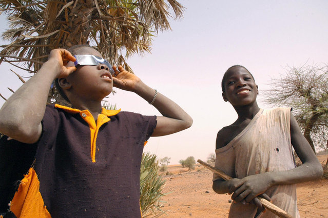Children watch a total solar eclipse in a village 30kms of Niamey, 29 March 2006. The moon blotted out the sun, turning day into night, in a total solar eclipse that carved a path from the tip of Brazil over northern Africa to the steppes of Mongolia. Thousands of astronomers and thrill-seekers gazed heavenward, prayers were said by the faithful and schools shut for the day as the three-hour celestial ballet raced across half the world. (Photo by Nicolas Postal/AFP Photo)