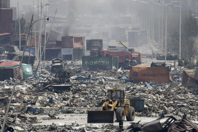 A bulldozer works near the site of the explosions at the Binhai new district, Tianjin, August 13, 2015. (Photo by Jason Lee/Reuters)
