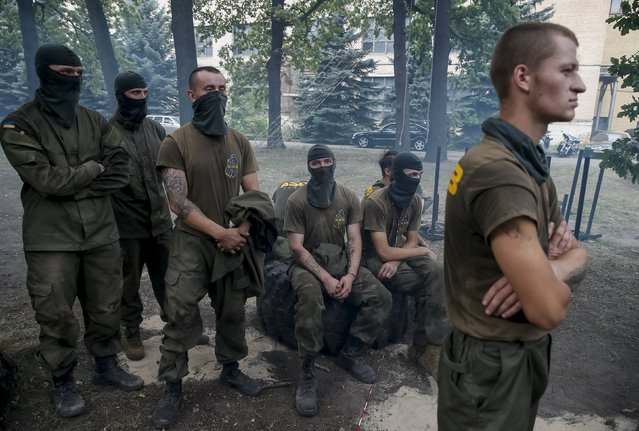 "New volunteers for the Ukrainian interior ministry's ""Azov"" battalion look on as they take part in tests before heading to frontlines in eastern Ukraine, at the battalion's training centre in Kiev, Ukraine, August 14, 2015. (Photo by Gleb Garanich/Reuters)"