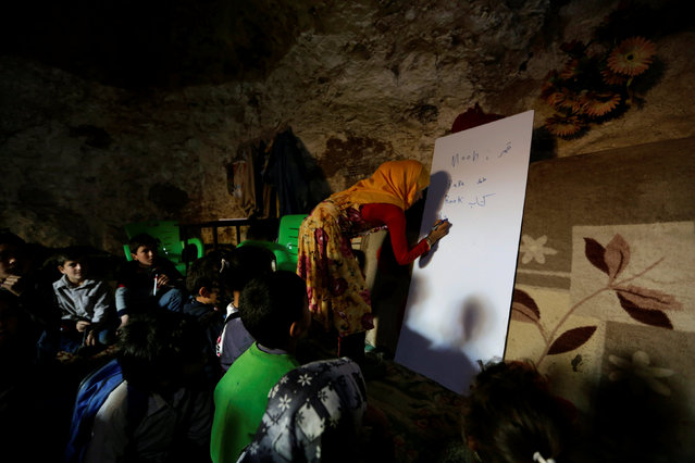A teacher conducts a lesson for internally displaced children inside a cave in the rebel-controlled village of Tramla, in Idlib province, Syria March 27, 2016. (Photo by Khalil Ashawi/Reuters)