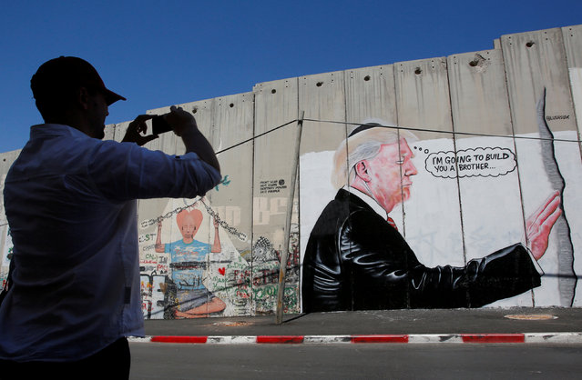 A man takes a photo of a graffiti depicting U.S President Donald Trump on the controversial Israeli barrier in the West Bank town of Bethlehem August 4, 2017. (Photo by Mussa Qawasma/Reuters)