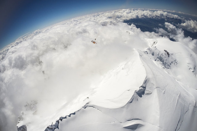 Fred Fugen and Vincent Reffet seen jumping at 33,000 feet (10 km) above the Mont Blanc, French Alps on May 31, 2014. Fearless skydivers jump from an altitude of 10,000 meters above the largest mountain in Europe. Frederic Fugen, 34, and Vincent Reffet, 29, leapt from a plane in the freezing skies above Mont-Blanc in the French Alps. The jump is from such a height the pictures show the curvature of the earth. (Photo by Dominique Daher/Barcroft Media)
