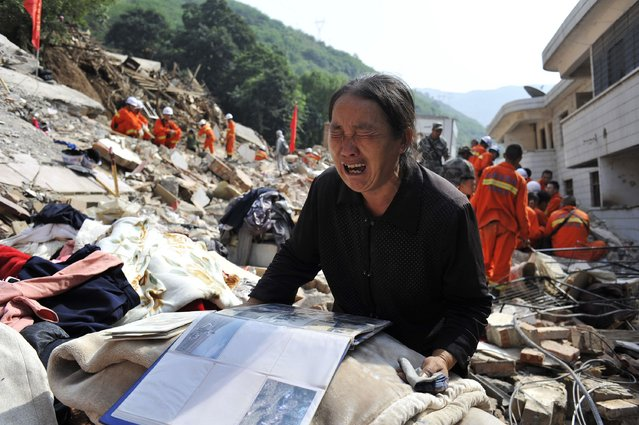 A woman cries over an album on the debris of her house at the earthquake zone of Longtoushan town, Ludian county, Zhaotong, Yunan province, August 6, 2014. An earthquake in China on the weekend triggered landslides that have blocked rivers and created rapidly growing bodies of water that could unleash more destruction on survivors of the disaster that killed 410 people, state media reported on Tuesday. (Photo by Reuters/Stringer)