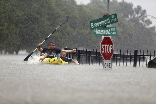 Two kayakers try to beat the current pushing them down an overflowing Brays Bayou along S. Braeswood in Houston, Texas, Sunday, August 27, 2017. Rescuers answered hundreds of calls for help Sunday as floodwaters from the remnants of Hurricane Harvey climbed high enough to begin filling second-story homes, and authorities urged stranded families to seek refuge on their rooftops. (Photo by Mark Mulligan/Houston Chronicle via AP Photo)