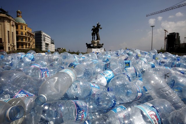 Water bottles are gathered to be recycled near a statue in Martyrs' Square in Beirut, Lebanon August 25, 2015.  Lebanon's cabinet held an emergency meeting on Tuesday in its newly fortified headquarters after protests over trash collection spilled over into street violence and calls for the feuding government to resign. (Photo by Jamal Saidi/Reuters)