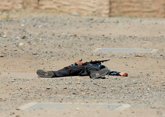 A role-playing actor lays on the ground after emerging with a weapon to fire at  Canadian soldiers from the Royal 22nd Regiment during a non-combative extraction operation in a simulated village  as part of Rim of the Pacific (RIMPAC) 2016 exercise held at Camp Pendleton, California United States, July 11, 2016. (Photo by Mike Blake/Reuters)