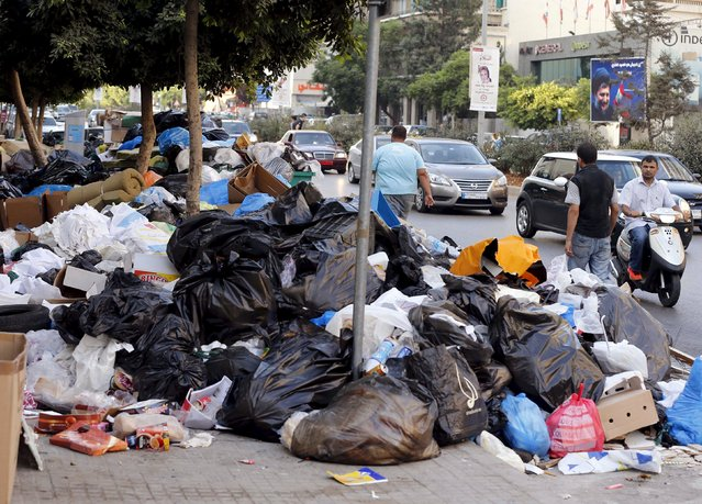 A man on a scooter, pedestrians and cars pass by garbage piled up along a street in Beirut, Lebanon August 26, 2015. The powerful Shi'ite party Hezbollah and its Christian allies walked out of an emergency Lebanese cabinet meeting on Tuesday in protest at a proposed solution to a garbage disposal crisis that has ignited violent protests in Beirut. (Photo by Mohamed Azakir/Reuters)