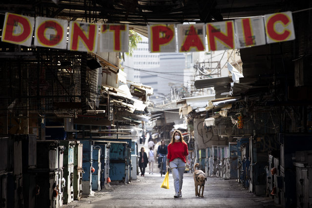 "A woman walks her dog under a ""don't panic"" sign hanging on the entrance of a food market that was shut down in order to reduce the spread of the coronavirus, in Tel Aviv, Israel, Monday, March 23, 2020. In Israel daily life has largely shut down with COVID-19 cases multiplying greatly over the past week. (Photo by Oded Balilty/AP Photo)"