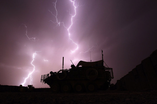 An armoured vehicle from the Centurion Company, 2-1 Infantry Battalion, 5/2 Stryker Brigade Combat Team is framed by a bolt of lightning during a storm at Combat Outpost Terminator in Maiwand District, Kandahar Province April 19, 2010. (Photo by Tim Wimborne/Reuters)