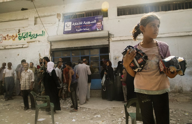 In this Friday, September 15, 2017 photo people queue outside a shop that recently opened after the breach of blockade, in Deir el-Zor, Syria. (Photo by AP Photo/Stringer)