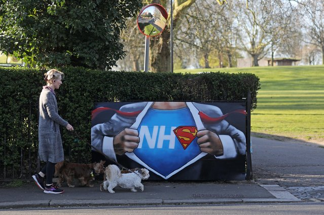 A dog walker walks past some Art on a wall in Hilly Fields park in support of the NHS, as the spread of the coronavirus disease (COVID-19) continues, London, Britain, April 5, 2020. (Photo by Simon Dawson/Reuters)