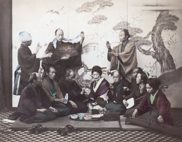 An elegant meal in Japan, circa 1865. The two ladies on the right are playing a shamisen and a koto, while a communal pipe is passed around. (Photo by Felice Beato/Spencer Arnold)