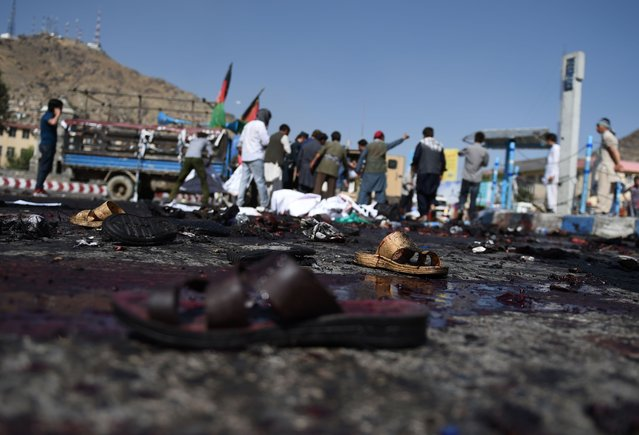 The sandals of Afghan protesters seen at the scene of a suicide attack that targeted crowds of minority Shiite Hazaras during a demonstration at the Deh Mazang Circle in Kabul on July 23, 2016. A powerful explosion on July 23, ripped through crowds of minority Shiite Hazaras in Kabul who had gathered to protest over a power line, killing at least 20 people and leaving 160 others wounded, officials said. No group has so far claimed responsibility for the blast, but it comes in the middle of the Taliban's annual summer offensive, which the insurgents are ramping up after a brief lull during the recent holy fasting month of Ramadan. (Photo by Wakil Kohsar/AFP Photo)
