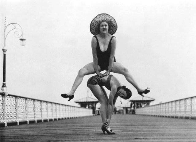 Holidaymakers enjoying a game of leap-frog on the pier at Llandudno. 16th August 1935.