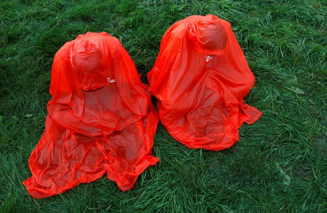 Pilgrims wearing raincoats pray before the opening ceremony of World Youth Day in Krakow, Poland, July 26, 2016. (Photo by David W. Cerny/Reuters)