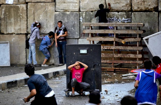 An injured protester takes cover behind a metal barrier during clashes with riot police behind cement blocks that are used to close the street leading to the U.S. Embassy in Cairo, Egypt. (Photo by Nasser Nasser\Associated Press)
