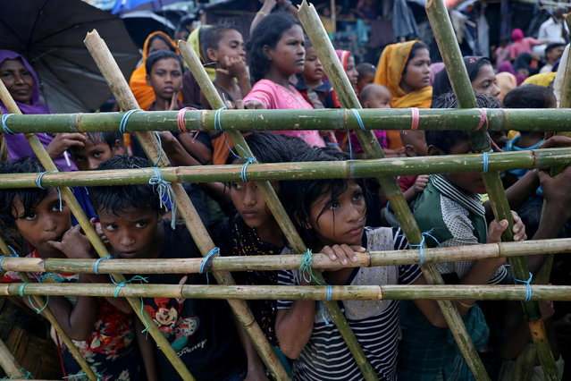 Rohingya refugees look through a fence as they wait outside of aid distribution premises at a refugee camp in Cox's Bazar, Bangladesh October 8, 2017. (Photo by Mohammad Ponir Hossain/Reuters)