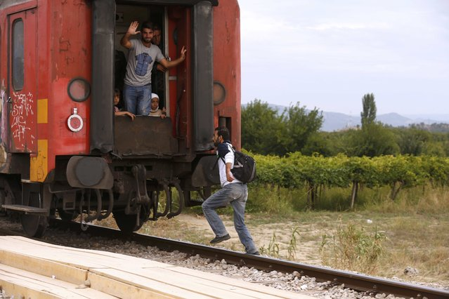 A migrant tries to get on a train which has already left the station near Gevgelija, Macedonia, September 7, 2015. (Photo by Stoyan Nenov/Reuters)