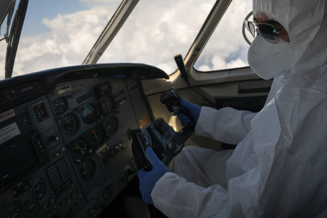 A pilot wearing personal protective equipment airlifts COVID-19 patients from Santo Antonio do Içá to a hospital in Manaus, Brazil, Tuesday, May 19, 2020. (Photo by Felipe Dana/AP Photo)