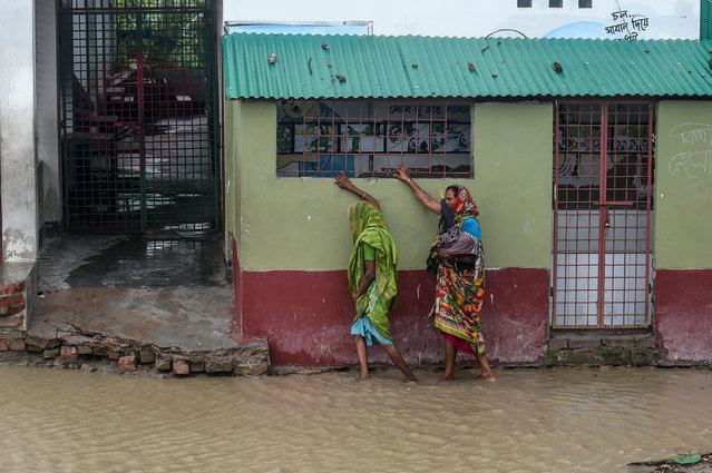 "Residents walk along a house on a flooded street heading to a shelter ahead of the expected landfall of cyclone Amphan, in Dacope of Khulna district on May 20, 2020. Several million people were taking shelter and praying for the best on Wednesday as the Bay of Bengal's fiercest cyclone in decades roared towards Bangladesh and eastern India, with forecasts of a potentially devastating and deadly storm surge. Authorities have scrambled to evacuate low lying areas in the path of Amphan, which is only the second ""super cyclone"" to form in the northeastern Indian Ocean since records began. (Photo by Munir Uz Zaman/AFP Photo)"