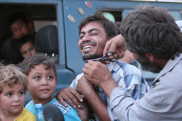 A man cuts the beard of a civilian who was evacuated with others by the Syria Democratic Forces (SDF) fighters from an Islamic State-controlled neighbourhood of Manbij, in Aleppo Governorate, Syria, August 12, 2016. (Photo by Rodi Said/Reuters)