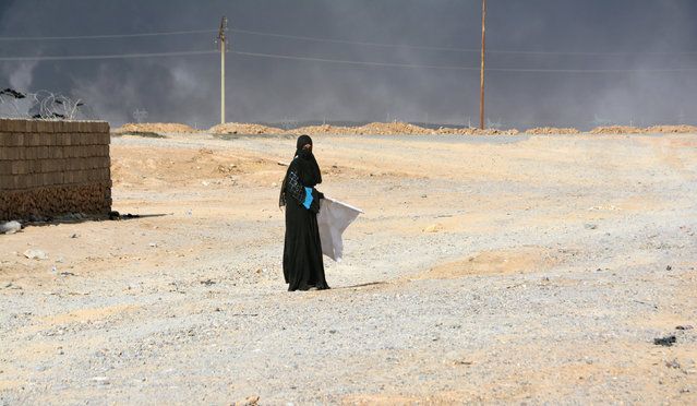 A displaced woman, who fled Islamic State violence, is seen on the outskirt of Al Qayyarah, Iraq, August 14, 2016. (Photo by Reuters/Stringer)