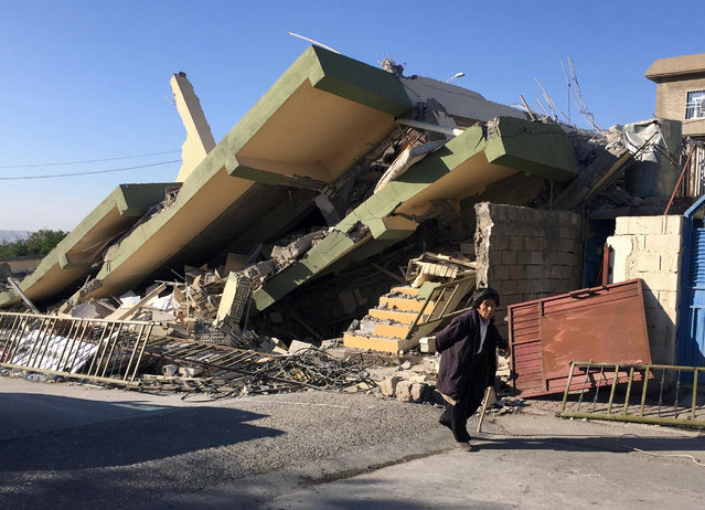 A man walks past a damaged building following an earthquake in Darbandikhan in Sulaimaniya Governorate, Iraq, Monday, November 13, 2017. (Photo by Ako Rasheed/Reuters)