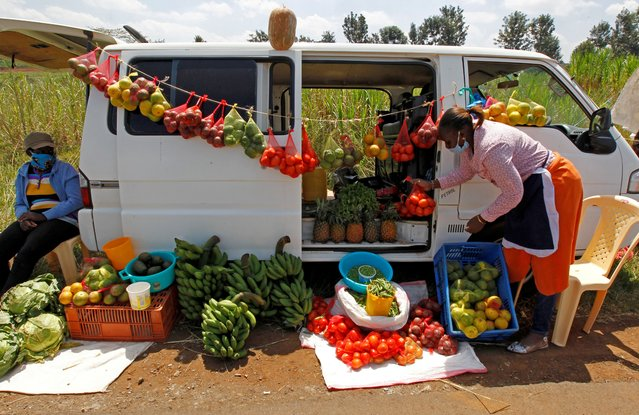 A motorist arranges fruits and vegetables for sale next to her vehicle, as an alternative mobile grocery stall, along the highway, following a lockdown due to the coronavirus disease (COVID-19) outbreak, on the outskirts of Nairobi, Kenya on May 25, 2020. (Photo by Njeri Mwangi/Reuters)
