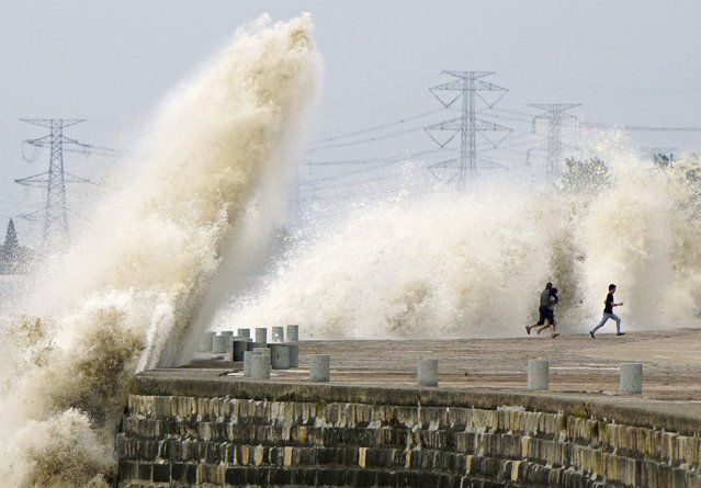 People run away from waves caused by a tidal bore which surged past a barrier on the banks of Qiantang River, in Haining, Zhejiang province October 8, 2014. (Photo by Reuters/China Daily)