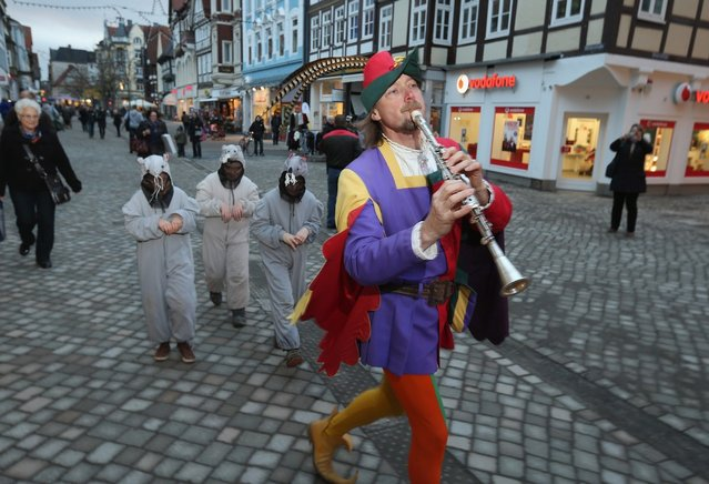 The Pied Piper of Hamelin, actually city tourism employee Michael Boyer, leads local children dressed as rats through a pedestrian shopping street on November 19, 2012 in Hameln, Germany. The Pied Piper (in German: Der Rattenfaenger), is one of the many stories featured in the collection of fairy tales collected by the Grimm brothers, and the 200th anniversary of the first publication of the stories will take place this coming December 20th. Boyer, a U.S. citizen who has lived in Hameln for 15 years, and city children regularly perform a reenactment of the Pied Piper tale throughout the summer months. The Grimm brothers collected their stories from oral traditions in the region between Frankfurt and Bremen in the early 19th century, and the works include such global classics as Sleeping Beauty, Little Red Riding Hood, Rapunzel, Cinderella and Hansel and Gretel.  (Photo by Sean Gallup)