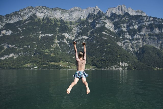 A boy jumps in the water of the Walensee lake at Murg, Switzerland, 27 August 2016. (Photo by Gian Ehrenzeller/EPA)