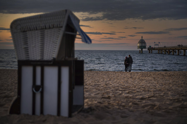In this Monday May 25, 2020 photo, two tourists stand on the beach on the Baltic island of Usedom near the city of Zinnowitz, Germany. Germany's states, which determine their own coronavirus-related restrictions, have begun loosening lockdown rules to allow domestic tourists to return. (Photo by Stefan Sauer/dpa via AP Photo)