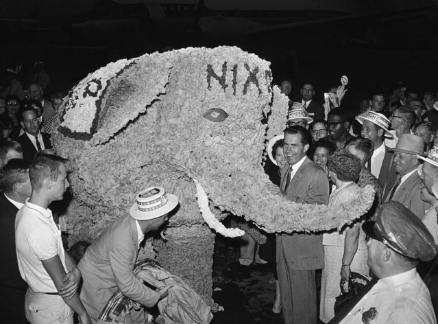 A crepe paper elephant draws a laugh from Vice President Richard Nixon during his campaign stop on September 23, 1960 in Kansas City, Mo. He came here from Sioux Falls, S.D. Four men, inside maneuvered the elephant. (Photo by AP Photo)