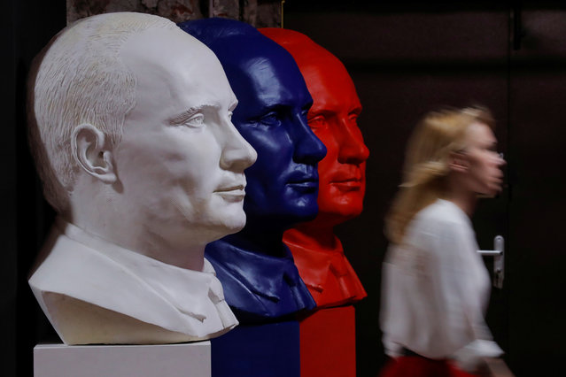 """A woman walks past busts depicting Russian president Vladimir Putin in the colours of the Russian national flag at the """"SUPERPUTIN"""" exhibition at UMAM museum in Moscow, Russia on December 6, 2017. (Photo by Maxim Shemetov/Reuters)"""