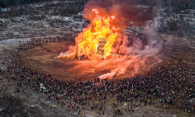 People watch a sculpture of a bridge burning at the Maslenitsa (Shrovetide) festival at the Nikola-Lenivets art park in Nikola-Lenivets village, about 200 kilometers (125 miles) south-west of Moscow, Russia, Saturday, February 29, 2020. Maslenitsa is a traditional Russian holiday marking the end of winter that dates back to the pagan times. (Photo by Dmitry Serebryakov/AP Photo)