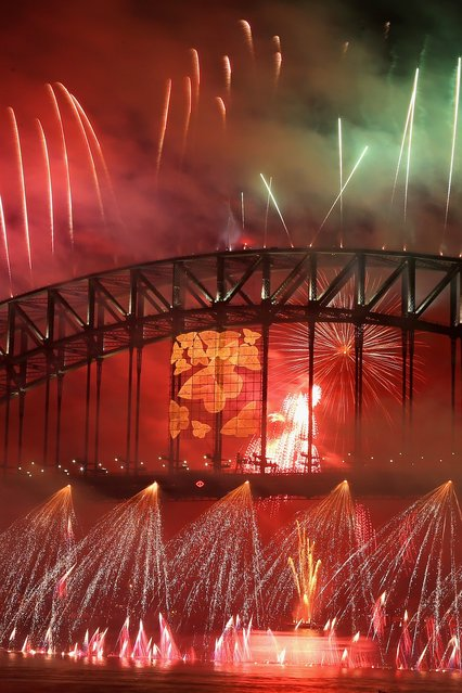 Fireworks light up the sky from The Sydney Harbour Bridge at midnight during New Years Eve celebrations on Sydney Harbour on December 31, 2012 in Sydney, Australia. (Photo by Cameron Spencer)